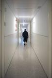 Paciente que camina solamente en un vestíbulo del hospital Foto de archivo
