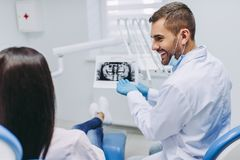 Paciente que discute com o dentista que olha o raio X imagens de stock