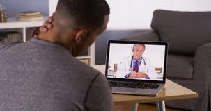 Paciente que discute problemas de saúde com o doutor em linha Foto de Stock