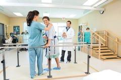 Paciente que es ayudado por el terapeuta físico Fotografía de archivo libre de regalías