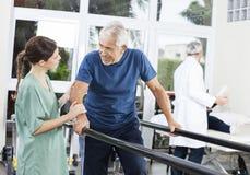 Paciente que mira al fisioterapeuta de sexo femenino While Walking Between foto de archivo libre de regalías
