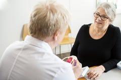 Paciente que mira el modelo del puño del doctor Explaining Shoulder Rotator foto de archivo libre de regalías