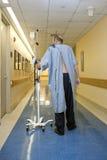Paciente que recorre abajo del pasillo del hospital Fotos de archivo libres de regalías