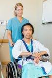 Paciente que se sienta en la silla de ruedas mientras que enfermera Foto de archivo
