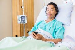 Paciente que sostiene el teléfono móvil mientras que descansa encendido Foto de archivo libre de regalías