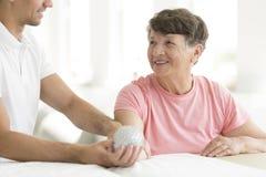 Paciente que sostiene la bola claveteada de la rehabilitación imagen de archivo libre de regalías
