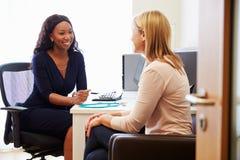 Paciente que tiene consulta con el doctor de sexo femenino In Office Imagenes de archivo