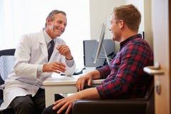 Paciente que tiene consulta con el doctor de sexo masculino In Office imagen de archivo libre de regalías