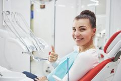 Paciente satisfeito que mostra seu sorriso perfeito após o tratamento em uma clínica do dentista foto de stock