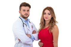Paciente sonriente de la mujer del doctor que tranquiliza joven sobre resultados médicos Aislado en blanco fotos de archivo