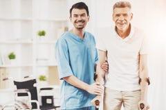 Paciente sonriente del doctor Helps Old Man con las muletas imagen de archivo