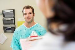Paciente sonriente que mira al doctor Imagenes de archivo