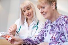 Paciente superior da mulher de Discussing Medication With da enfermeira fêmea fotos de stock royalty free