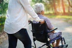 Paciente superior ou idoso asi?tico da mulher da senhora idosa com cuidado, ajuda e apoio na cadeira de rodas no parque no feriad imagem de stock royalty free