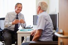 Paciente superior tendo a consulta com doutor In Office Foto de Stock