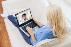 Paciente tendo a chamada video com o doutor no portátil imagem de stock