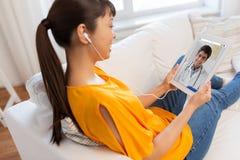 Paciente teniendo charla video con el doctor en la PC de la tableta imagen de archivo