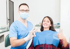 Paciente y dentista que muestran el pulgar para arriba y muy bien Imagen de archivo