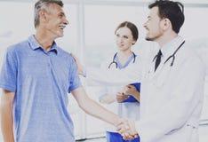 Paciente y su doctor confiado Shake Hands Foto de archivo