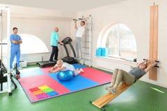 Pacientes que exercitam sob a supervisão do fisioterapeuta fotografia de stock