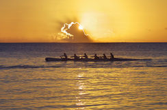 Pacific Canoe at Sunset. Men rowing a canoe at the Pacific Ocean at sunset Stock Photos