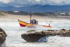 Dory Boat approaches landing on beach Stock Photo