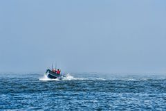 Dory boat coming in out of the fog Stock Images
