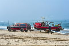 Dory boat being hauled off of beach Stock Image