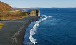 Pacific Coast with black volcanic sand on the beach. Kamchatka. Panoramic view of Pacific Coast with black volcanic sand on the beach. Beautiful autumn landscape royalty free stock photography