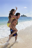 Pacific island man carries a young woman Stock Photo