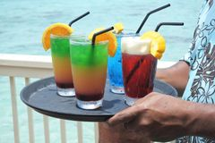 Pacific islander male waiter serving cocktails on a tropical pac. Ific island resort in Rarotonga, Cook Islands. Drinks background. Copy space Royalty Free Stock Image
