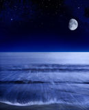 Pacific Moon. The moon glowing over a calm Pacific ocean shortly after sunset Stock Images