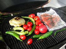 Pacific Northwest barbecue - salmon on foil. Tomatoes, squash and peppers on a grill Stock Images