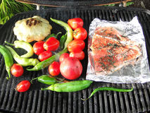 Pacific Northwest barbecue - salmon on foil. Tomatoes, squash and peppers on a grill Royalty Free Stock Image
