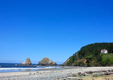 Pacific Northwest Beach. In the summer, huge rocks in the water, green trees on the hillside.  Room for text Stock Image