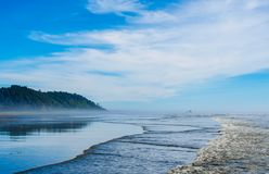 Pacific Northwest ocean beach shoreline. Beautiful seaside waves splashing onshore with distant mountain hills reflecting in wet sands Stock Image