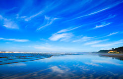 Pacific Northwest ocean beach shoreline. Clouds reflecting on wet sand. Pacific northwest ocean beach shoreline.  Wispy clouds and vibrant blue skies reflecting Stock Photo