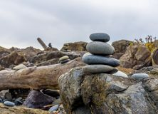 Pacific Northwest Zen. Balance and wellness concept. Close-up of ocean stones balanced on rocks and ocean driftwood. Low depth of field. Zen and spa inspired royalty free stock photo