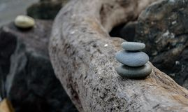 Pacific Northwest Zen. Balance and wellness concept. Close-up of ocean stones balanced on rocks and ocean driftwood. Low depth of field. Zen and spa inspired stock photography
