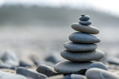 Pacific Northwest Zen. Balance and wellness concept. Close-up of ocean stones balanced on rocks and ocean driftwood. Low depth of field. Zen and spa inspired royalty free stock image