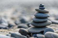 Pacific Northwest Zen. Balance and wellness concept. Close-up of ocean stones balanced on rocks and ocean driftwood. Low depth of field. Zen and spa inspired royalty free stock photos