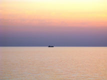 Pacific ocean with clear horizon, purple sunset skies and ship on horizon Royalty Free Stock Photo