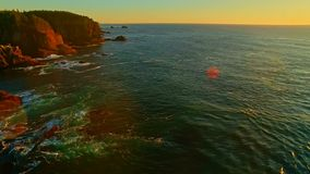 Pacific ocean coast bay at sunset. Sweeping motion shot of Pacific ocean golden shore waves at sunset, rocky cliffs, cinematic, colorful, coastal ocean view stock video footage