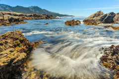 Pacific Ocean currents rush into bay with bubbles Stock Image