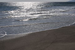 Pacific ocean with glistening sun on the sand Royalty Free Stock Photo
