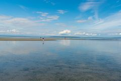 Pacific Ocean reflecting blue sky and clouds in Delta, BC, Canada. Delta, British Columbia/Canada - June 10, 2017: families play in the water and explore royalty free stock images
