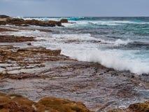 Pacific Ocean Waves on Bondi Rocks, Sydney, Australia. White foam surf Pacific Ocean waves washing and crashing over sandstone rocks at North Bondi Beach, Sydney stock photos