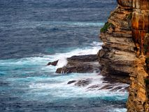 Pacific Ocean Waves Breaking on Rocks at Base of Cliff Royalty Free Stock Image