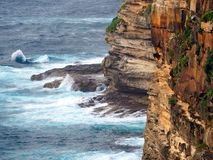 Pacific Ocean Waves Breaking on Rocks at Base of Cliff Stock Photography