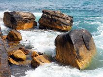 Waves Swirling Around Sandstone Rocks, Manly, Australia. Pacific Ocean waves breaking and swirling around large Sydney sandstone rocks at the waters edge, Manly Stock Image